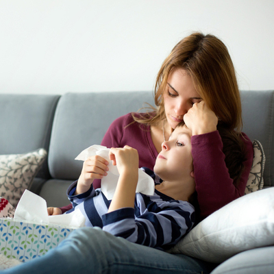 Moeder met ziek kind op de bank
