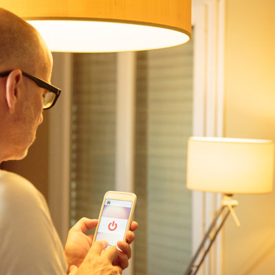 Man stel met smartphone verlichting in
