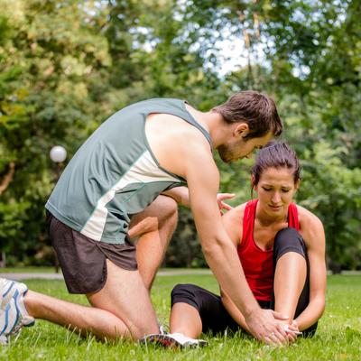 Eerste hulp bij sporters - Man helpt vrouw met pijnlijke enkel
