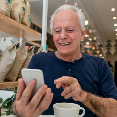 TOK - oudere man met mobieltje en kopje koffie