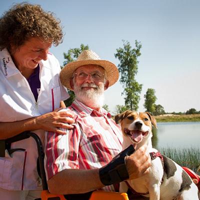 Man in rolstoel met hondje en medewerker Comfortzorg